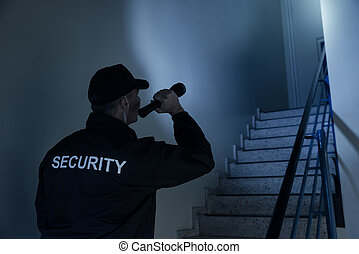 Security Guard Searching On Stairway With Flashlight - Rear...