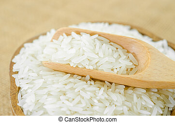 Raw white rice - Raw white rice and wooden spoon in cup on...
