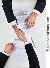 Businessman Shaking Hands With Male Candidate At Desk