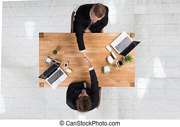 Businessmen Shaking Hands At Desk In Office