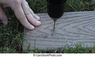 Man drilling hole in wood - This is a video of a man...