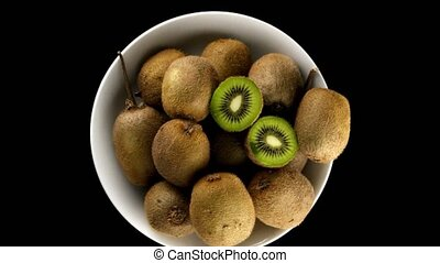 Kiwi in a white mug rotating on black background. Top view