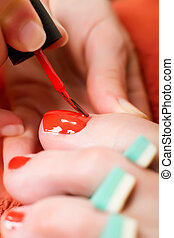 Pedicure. - Closeup of a womans toes being painted with red...