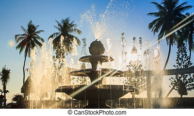 closeup round fountain operates changing jets in tropical...