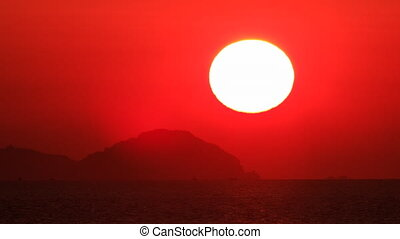 large red sun disk appears from behind cloud sea at foreground