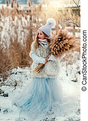 Pretty girl in winter with reed - cute little girl in a fur...