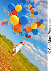 courage - child running with a bunch of colorful balloons in...