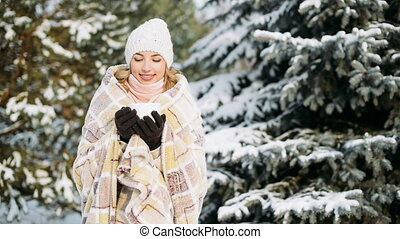 Girl drinks outdoors in winter forest