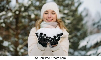 Woman in winter hat blows off snow from hands