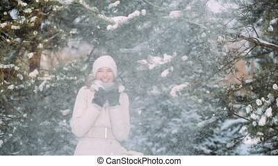 Snow falls on a girl with tree branches