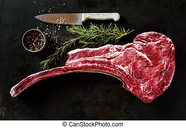 Raw tomahawk beef steak with ingredients for grilling with a...