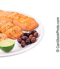 Fried salmon fillet on plate with lemon Isolated on a white...