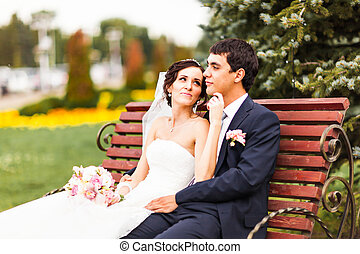 The bride and groom sitting on a bench in the Park.