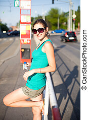 Pretty, young woman waiting for a streetcar/tramway
