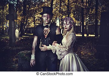 Dressed in wedding clothes romantic zombie couple walking on...