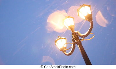 Vintage lampposts and falling snow - Christmas evening with...