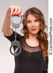Sexual woman demonstrating handcuffs - Holding handcuffs...