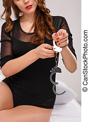 Attractive young woman fiddling with handcuffs - Opening...
