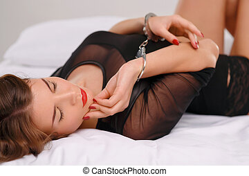 Sexual young woman lies in bed locked with handcuffs -...
