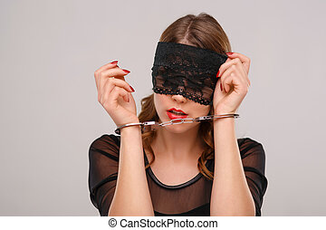Sexual woman in eyeshade locked with handcuffs - Hands...