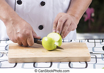 cutting green apple - Chef's hands cutting green apple on...