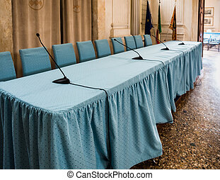 Conference table with black microphones and blue chairs -...