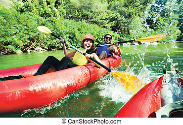 fun splashing canoe river - A female and a male in red...