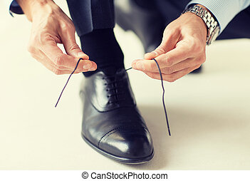 close up of man leg and hands tying shoe laces - people,...