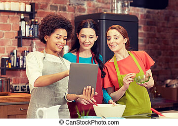 happy women with tablet pc cooking in kitchen - cooking...