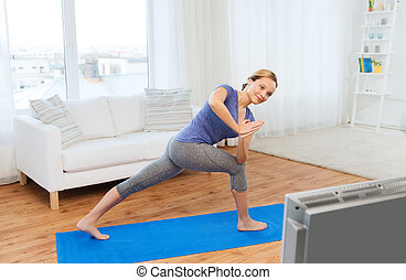woman making yoga low angle lunge pose on mat - fitness,...