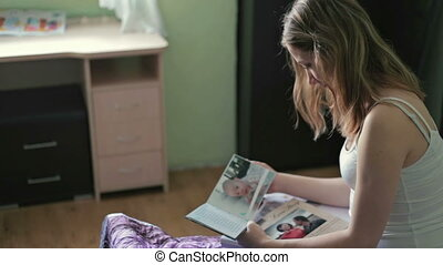 Close up Young Woman Looking At Photobook in bedroom - Close...