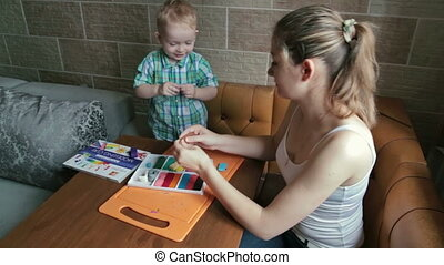 Mother and son playing with plasticine