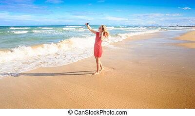 Blond Slim Girl Walks along Beach Makes Selfie in Red