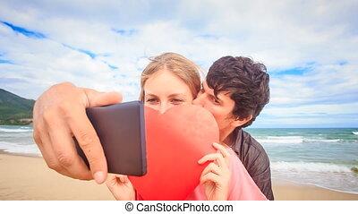 Guy Blond Girl Make Selfie Kiss Hide behind Red Heart on Beach
