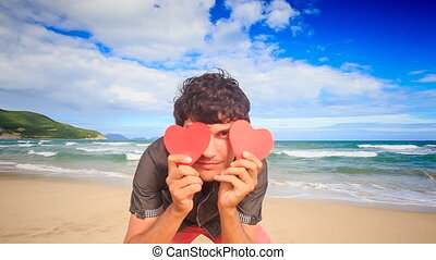 Guy Hides Face behind Red Hearts Smiles on Wave Surf Beach -...