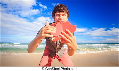 Guy Shows to Camera Red Hearts Gift on Wave Surf Beach -...
