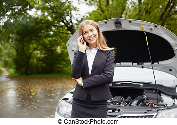 Smiling woman calling someone for help with his broken car