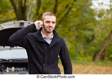Young man with a broken car calling for assistance