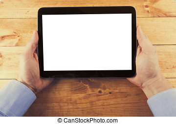 digital tablet with blank screen in hands on the wooden table