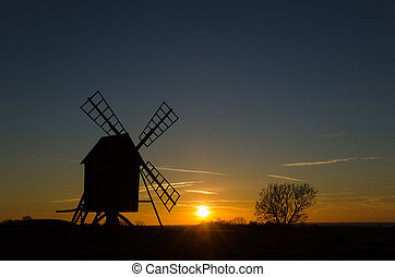Sunset with silhouette of an old windmill
