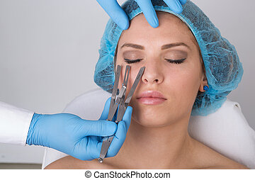 Young woman getting a permanent eyebrow make up treatment -...