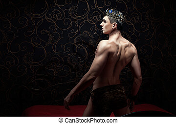 Handsome man wearing crown standing on a bed. In a dark...