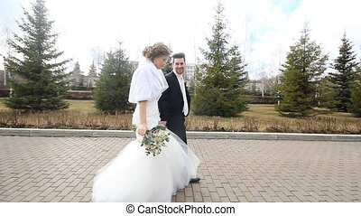 Wedding couple, beautiful young bride and groom standing in a park