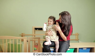 Female teacher with little girl in kindergarten