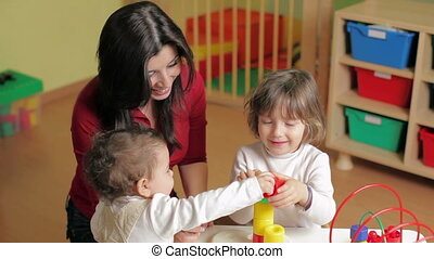 two little girls and female teacher in kindergarten - female...