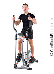 young man doing exercises on elliptical trainer - young cute...