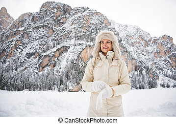 Woman in coat and fur hat wearing gloves while standing outdoors