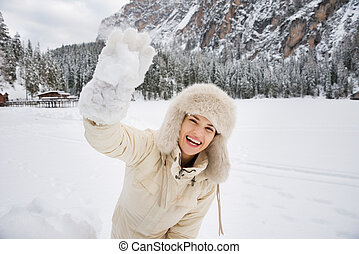 Woman in white coat and fur hat throwing snowball outdoors -...