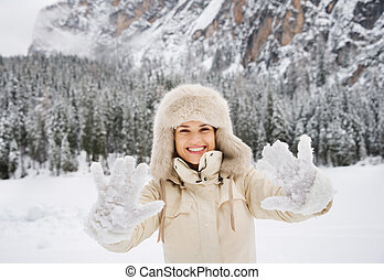 Woman in coat and fur hat showing snow-covered mittens...