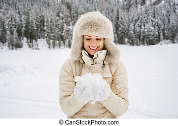 Woman looking on snow in hands while standing outdoors -...